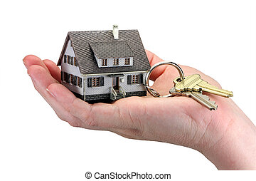 Concept image of a hand holding house keys. The miniature model house acts as a key ring with house keys hanging from it. White background.