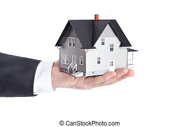 Realty concept - hand holding house architectural model, isolated
