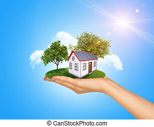 Hand holding house on green grass with tree, solar panels. Background clouds, blue sky