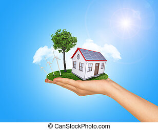 Hand holding house on green grass with tree, solar panels, wind turbine. Background clouds, blue sky