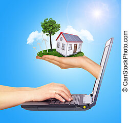 Hand holding house on green grass with tree, solar panels, wind turbine of screen laptop. Background clouds, blue sky