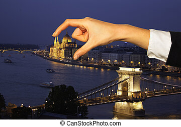 Hand holding Hungarian Parliament Building on background