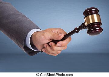 Hand holding judge mallet