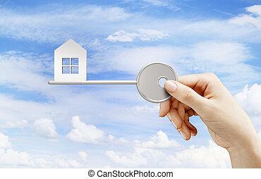 hand holding key house on sky background