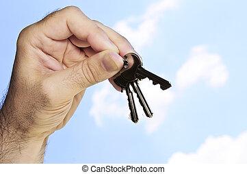 Hand holding keys - Man\\\'s hand holding house keys on blue...