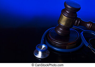 Hand holding law gavel - Wooden law gavel with stethoscope -...