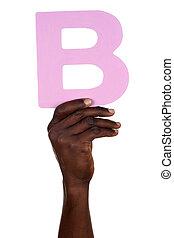 Hand holding letter B from alphabet