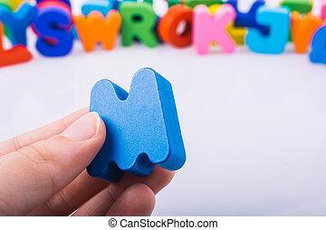 Hand holding Letter cube M of Alphabet