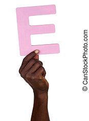 Hand holding letter E from alphabet