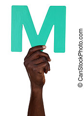 Hand holding letter M from alphabet