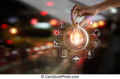 Hand holding light bulb in front of global show the world's consumtion with icons energy sources for renewable, sustainable development. Ecology and enviroment concept. Elements of this image furnished by NASA.