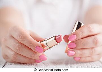 Hand holding lipstic on white background