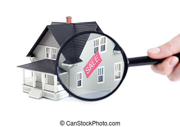 Hand holding magnifying glass in front of the house