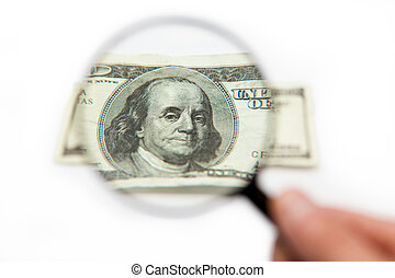 Hand holding magnifying glass over dollar bill