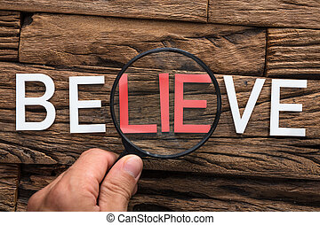 Hand Holding Magnifying Glass Over Word Lie In Believe