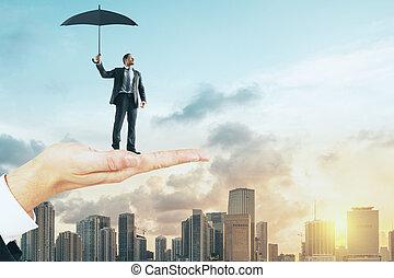Hand holding man with umbrella