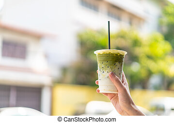 hand holding matcha green tea cup