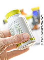 Hand holding medicine bottle