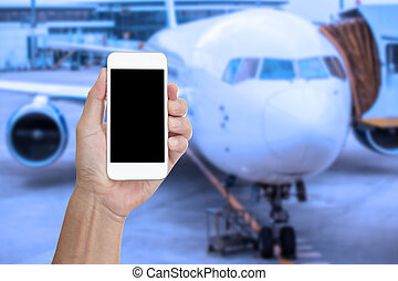 Hand holding mobile phone with blank screen and blur airplane background