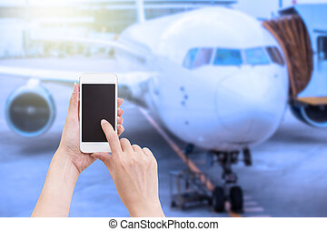 Hand holding mobile phone with blurred image of airplane background