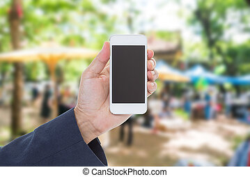 Hand holding mobile phone with blurred street market background