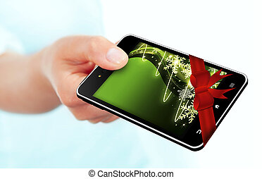 hand holding mobile phone with christmas screen and ribbon isolated over white background. Focus on mobile phone.
