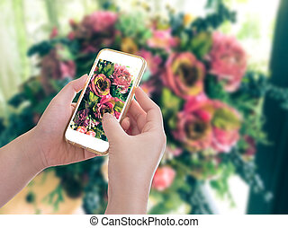 Hand holding mobile phone with flower bouquet background