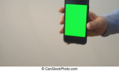 Hand holding mobile phone with green screen. Chroma key.