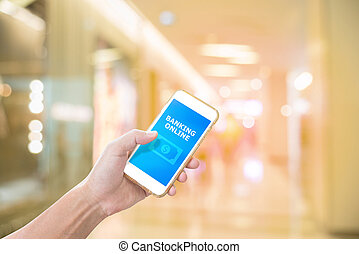Hand holding mobile phone with mobile banking application on screen