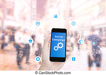 Hand holding mobile phone with Social campaign word on double exposure night cityscape and abstract blur business people
