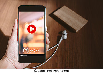 Hand holding mobile watching viral video advertising on ...
