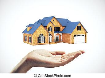 Hand holding model modern cottage.