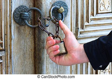 Hand holding old iron security lock of ornamental wooden...