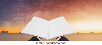 Hand holding opened book, blank pages on colorful starry sky. Concepts of imagination, knowledge, wisdom and education