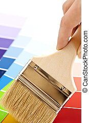 Hand holding paintbrush over color card samples