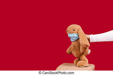 Hand holding pandemic Easter bunny toy wearing medical mask looking to empty space. COVID 19 holiday on red background. Concept for health, holidays during quarantine, celebration, restrictions.
