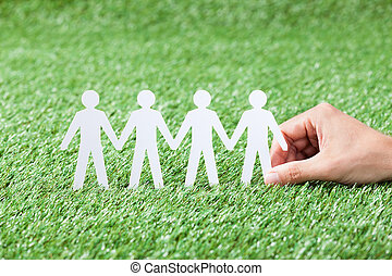 Hand Holding Paper People Chain On Grass