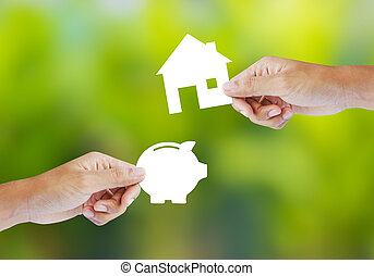 piggy bank and house shape - Hand holding paper piggy bank...