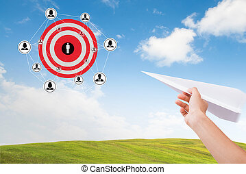 Hand holding paper plane with marketing goals dartboard on sky. concept setting target vision.