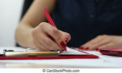 hand holding pen and writing on clipboard