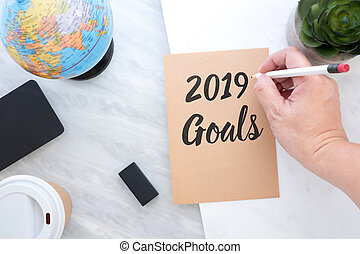 Hand holding pen writing 2019 Goals on brown paper with blue globe, blackboard, coffee cup on marble table. new year?s resolutions concept.