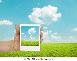 Hand holding photograph of landscape with landscape in background
