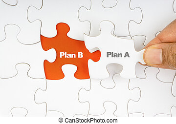 Hand holding piece of jigsaw puzzle with word PLAN A & PLAN B