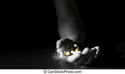 Hand holding pills and white powder dropping dead in slow motion