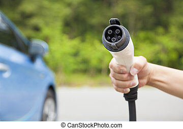 hand holding plug in connector for Charging electric car