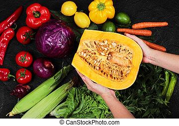 Hand holding pumpkin and variety of fresh vegetables on balack table