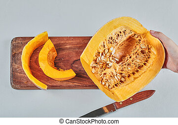 Hand holding pumpkin on wooden chopping board with knife