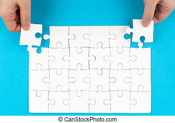 puzzle - Hand holding puzzle pieces and inserting them into...