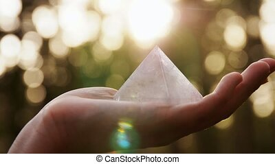 occult science and supernatural concept - hand with pyramid performing magic ritual in forest