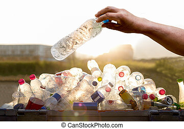 Hand holding recyclable plastic bottle in garbage bin with ...